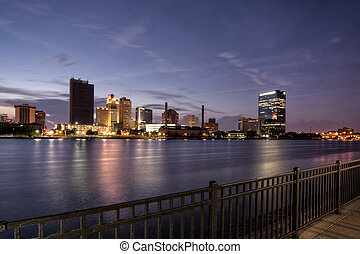 A panoramic view of downtown Toledo Ohio's skyine at night from across the Maumee river. A beautiful purple and blue sky with the city lights reflecting into the Maumee river.