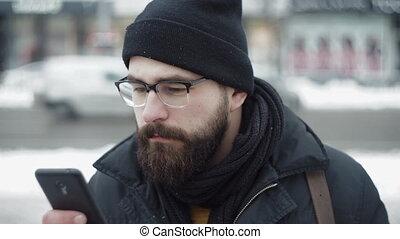 City man uses smartphone and drinking tea on winter street