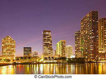City of Miami Florida, night skyline. Cityscape of residential and business buildings lit by bright lights after sunset