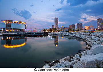 Image of Milwaukee skyline at twilight with city reflection in lake Michigan and harbor pier.