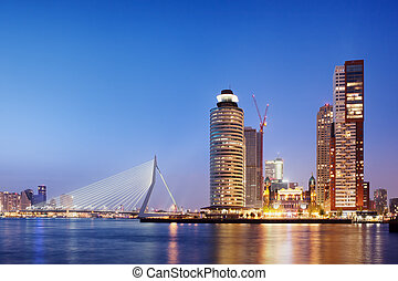 City of Rotterdam downtown skyline at dusk in South Holland, Netherlands, Erasmus Bridge on the left.