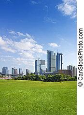 city park - City park under blue sky with Downtown Skyline...