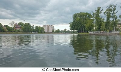 Low angle panoramic view from quay of Upper Lake - artificial city pond, famous tourist sight and popular leisure zone in Kaliningrad, Russia at springtime on cloudy day rendered in 4K