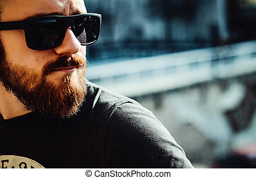 city portrait of a young guy with a beard and glasses on the street