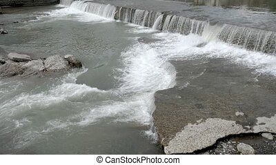 City river with rapids. Strong current. Summer day