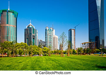 modern office building and green park in shanghai china.