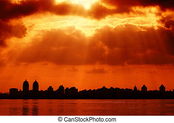 City silhouette and red sky with sun rays