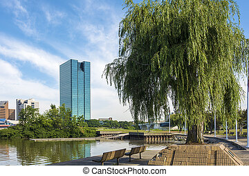 A panoramic view of downtown Toledo Ohio's skyline from across the Maumee river. A beautiful blue sky with white clouds for a backdrop.