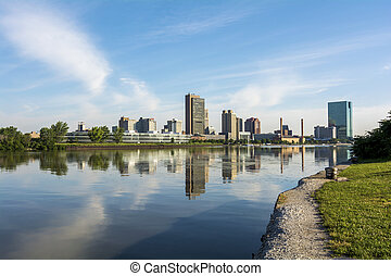 A panoramic view of downtown Toledo Ohio's skyline from across the Maumee river. A beautiful blue sky with white clouds reflecting into the water.