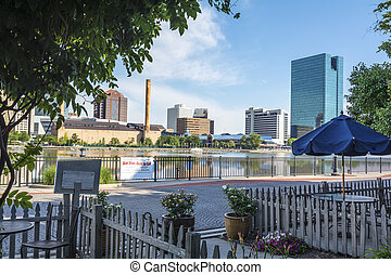 A panoramic view of downtown Toledo Ohio's skyline from across the Maumee river at a popular restaurant area with a paver brick boardwalk and a decorative iron railing.. A beautiful blue sky with white clouds for a backdrop.