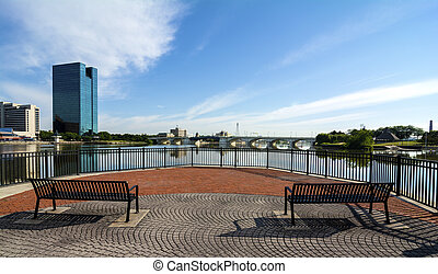 A panoramic view of downtown Toledo Ohio's skyline from across the Maumee river at a popular restaurant area with a paver brick boardwalk and a decorative iron railing and park benches to enjoy the view. A beautiful blue sky with white clouds for a backdrop.