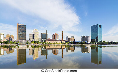 A panoramic view of downtown Toledo Ohio's skyline reflecting into the Maumee river. A beautiful blue sky with white clouds for a backdrop.