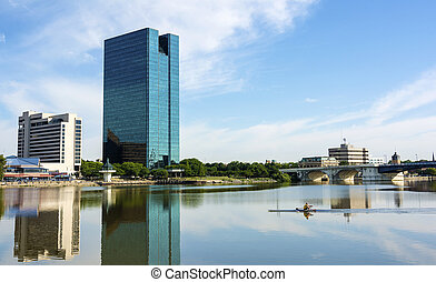 A panoramic view of downtown Toledo Ohio's skyline reflecting into the Maumee river a with a man rowing on the water. A beautiful blue sky with white clouds for a backdrop.