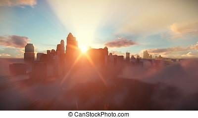 City skyline against sunset, flight over clouds