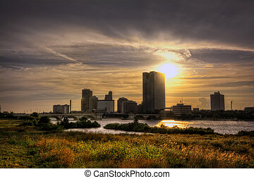 A panoramic view of downtown Toledo Ohio's skyine at sunset from across the Maumee river. A beautiful glow of colors reflecting in the clouds and n the grass in the foregrond.