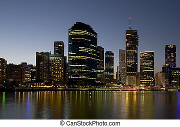 city skyline with river in foreground at dusk