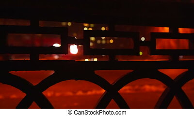 City street at night in winter. View through the iron fence...
