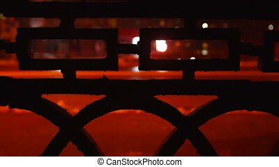 City street at night in winter. View through the iron fence