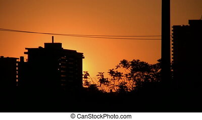 Fast timelapse shot of sun rising in the city. Condos in silhouette. Toronto, Ontario, Canada.