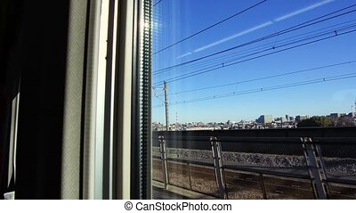 city view from window of moving train or railway -...