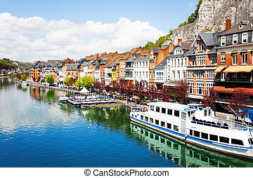 City view of Dinant on Meuse river with ships and houses...