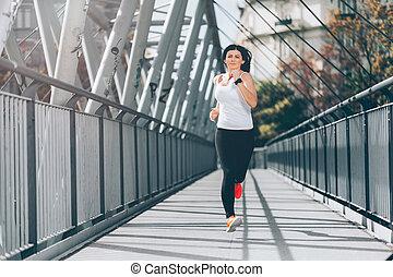 City workout. Beautiful woman running in an urban setting -...