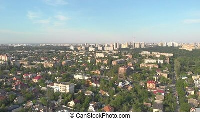 Cityscape aerial drone view long shot big city TV tower houses apartment buildings blue sky sunset Kyiv Ukraine forward movement