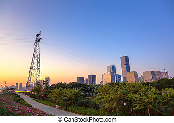 Cityscape at dusk including a large vertical steel tower ...
