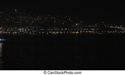 Cityscape At Night With Ship On The Water