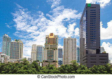 Cityscape behind a public park with blue sky background.