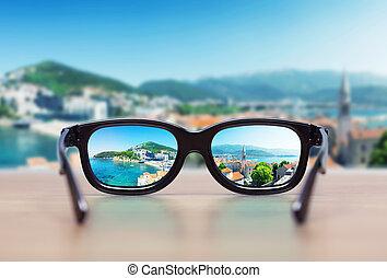 Cityscape focused in glasses lenses. Vision concept