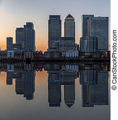 Cityscape landscape at sunset reflected in calm waters of lake