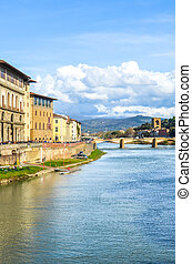 Cityscape of beautiful Florence, Tuscany, Italy photographed from the famous Ponte Vecchio Bridge. Historical buildings including Galleria degli Uffizi along the Arno river. Vertical photo.