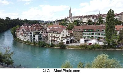 Aerial view of cityscape of old town of Bern, Switzerland, with Cathedral Bell Tower reflecting into Aare river. Popular landmark of historical town UNESCO World Heritage. Skyline of medieval houses.
