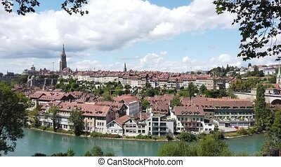 Aerial view of cityscape of old town of Bern, Switzerland, with Cathedral Bell Tower and Aare river. Popular landmark of historical town UNESCO World Heritage. Skyline of medieval houses.