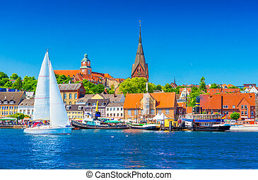 Cityscape of Flensburg. Panorama of a small European town in Northern Germany. A sailboat is floating in a harbour along the coastline with old architecture, ships and landmarks on the background