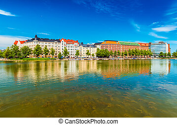 Cityscape of Helsinki reflected in water. Historical buildings with blue sky on the background, Finland