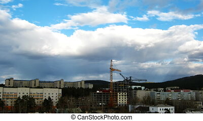 Cityscape with construction site and dramatic sky. Timelapse
