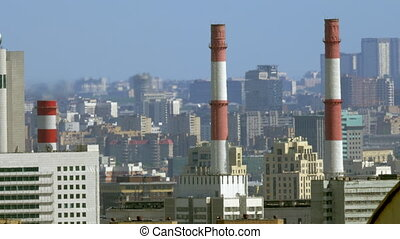 Cityscape with factory pipes in foreground - City view with...
