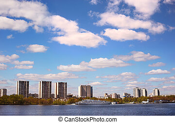 cityscape with spring cloudy sky, houses and river bank