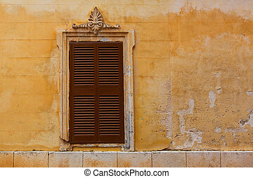 Ciutadella Menorca wooden shutter window on grunge yellow...
