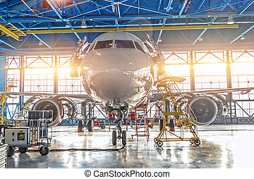 Civil airplane jet on maintenance of engine and fuselage check repair in airport hangar. Bright light at the gate