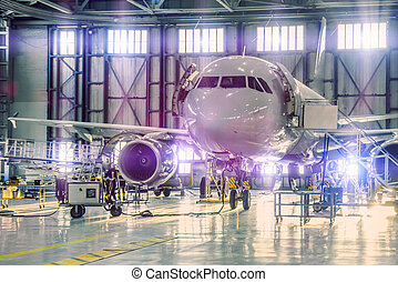 Civil airplane jet on maintenance of engine and fuselage check repair in airport hangar. Bright light purple tint at the gate.