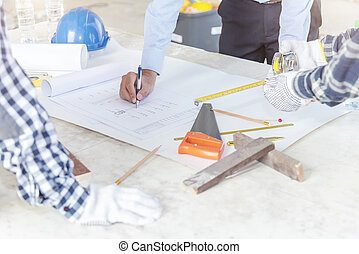 Civil engineer and foreman meeting and working on blueprint. Architects workplace, architectural project blueprints ruler calculator.