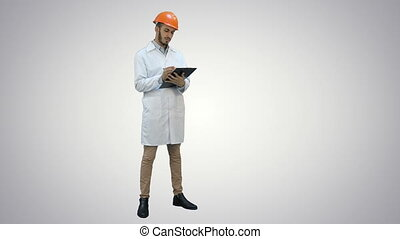 Civil engineer in white coat preparing report on white...