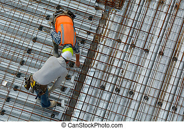 Civil engineer inspecting the work progress of a worker in a...