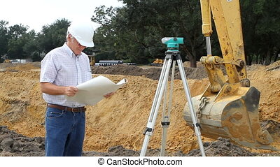 Civil engineer reads architectural blueprints and inspects the work at a construction site.