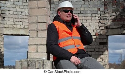 Civil engineer sitting and talking on smart phone