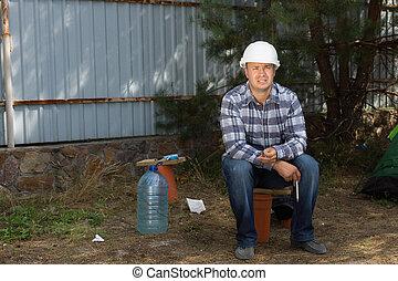 Civil Engineer Sitting at Construction Site Corner