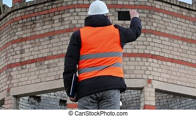 Civil engineer take pictures on tablet PC near building